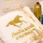 Вышивка золотой нитью на белом махровом халате изображения коня и надписи Любимый охотник